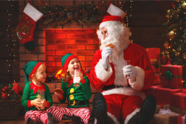 santa sitting with children who are dressed as elves