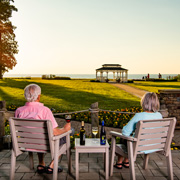 older couple sitting in chairs looking out towards a gazebo and lake