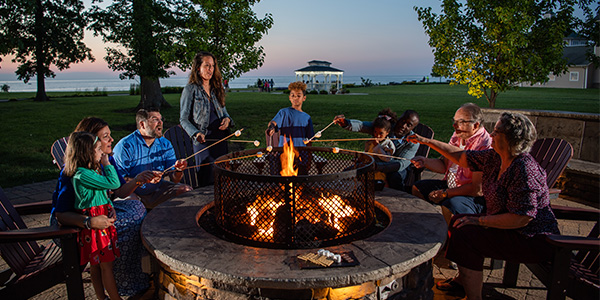 kids and adults hanging out by a camp fire roasting smores