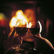 Two people touching wine glasses together