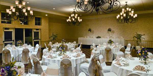 The Lodge at Geneva-on-the-Lake's grand ballroom is set up for a wedding reception featuring chairs with blush-colored seatback cover ties