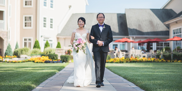 A bride walks down the wedding aisle at The Lodge at Geneva-on-the-Lake with her father