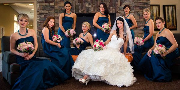 A bride and eight bridesmaids pose together inside The Lodge at Geneva-on-the-Lake during a wedding