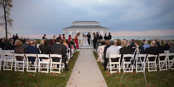 A bride and groom get married in a gazebo overlooking Lake Erie at sunset with wedding guests watching their ceremony