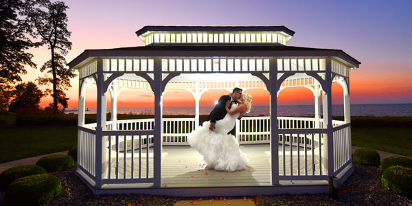 A bride and groom kiss at sunset in a gazebo overlooking Lake Erie at The Lodge at Geneva-on-the-Lake