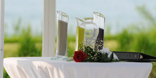 Several containers of sand stand together before an outdoor wedding sand ceremony at The Lodge at Geneva-on-the-Lake